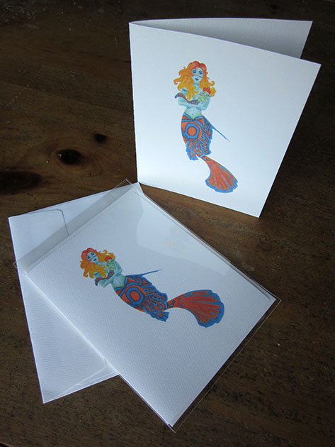 colorful mermaid holding a mer-baby card design